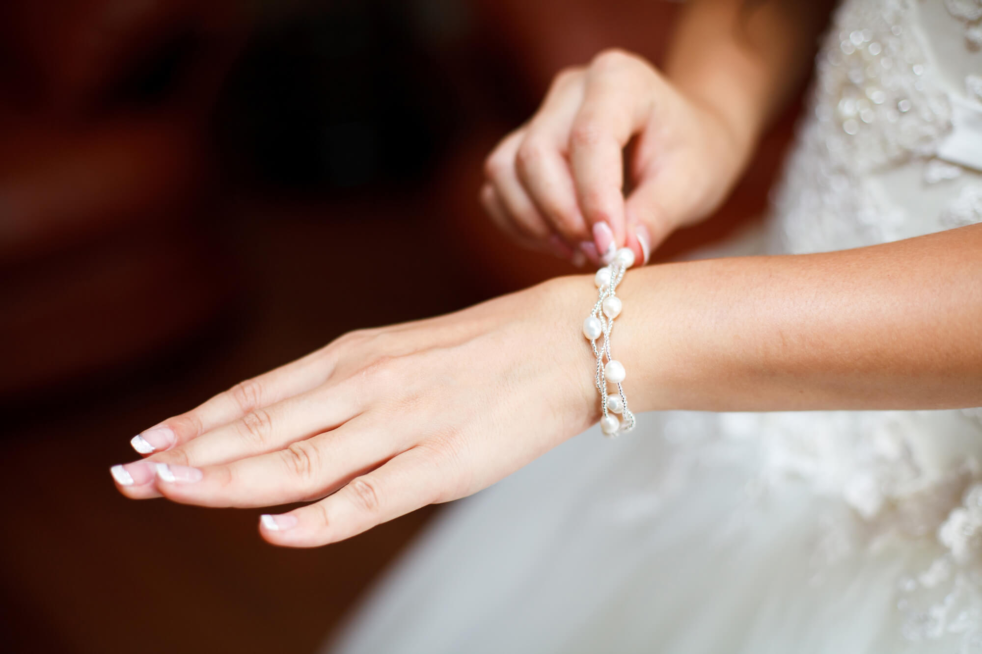 水晶のブレスレットを着ける手